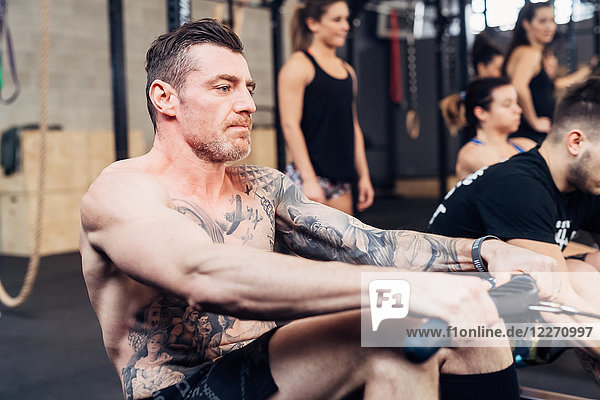 Tattooed man using exercise equipment in gym