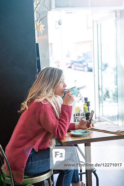 Woman sitting in cafe  drinking coffee  holding smartphone