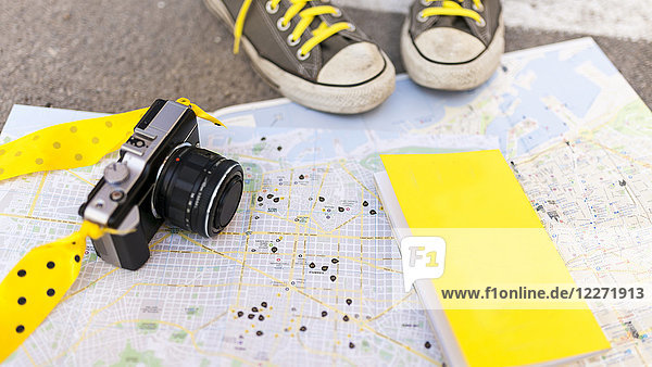 Close-up of sneakers  book and camera on city map