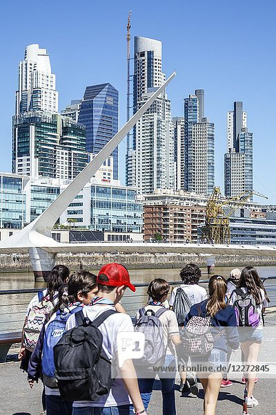 Argentina  Buenos Aires  Puerto Madero  Rio Dique  water  riverfront  city skyline  promenade  Puente De La Mujer  pedestrian suspension swing bridge designed architect Santiago Calatrava  Hispanic  boy  girl  teen  walking  backpack  Argentinean Argentinian Argentine South America American