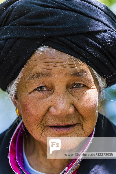Woman of the Bai ethnic minority wearing a characterisitic tunic  Black Dragon Pool Park  Lijiang  Yunnan Province  China.