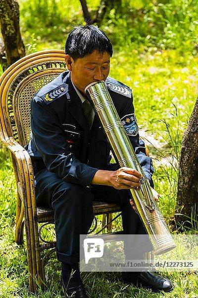 A man smokes a cigarette through a bong in the ancient village of Baisha  near Lijiang  Yunnan Province  China.