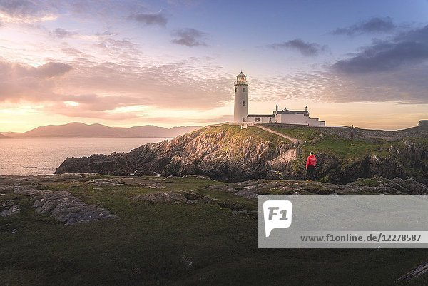 Fanad Head (Fánaid) lighthouse  County Donegal  Ulster region  Ireland  Europe. A photographer on the field at sunrise near Fanad Head lighthouse.