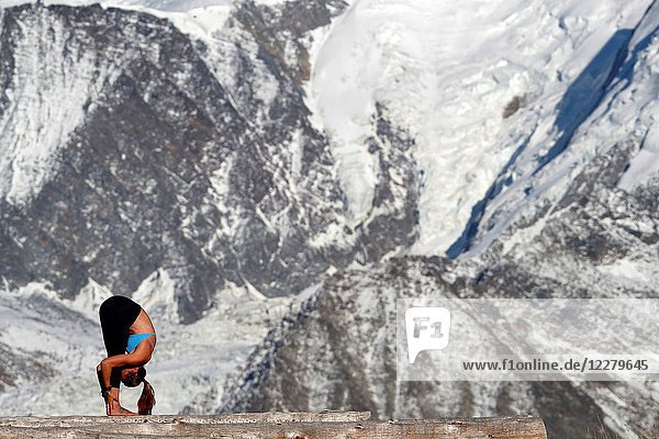 French Alps. Mont-Blanc massif. Woman doing yoya meditation on mountain.