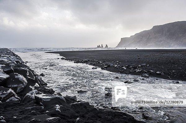 A stream in the black sands beach of Vík and Reynisdrangar rocks (region of Suðurland  Iceland).