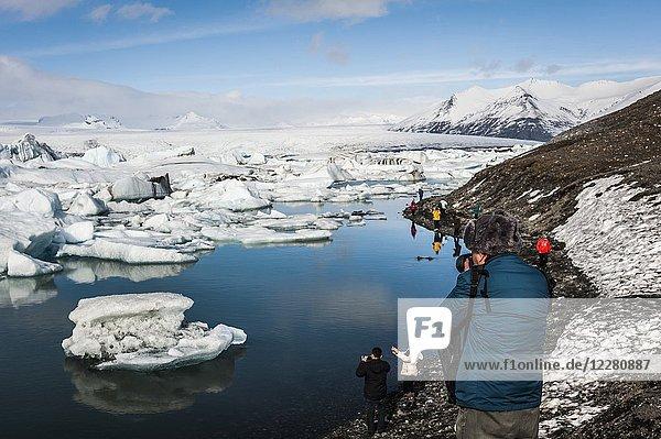 Tourists taking pictures to icebergs in Jökulsárlón Glacier Lagoon  Breidamerkurjökull Glacier (region of Austurland  Iceland).