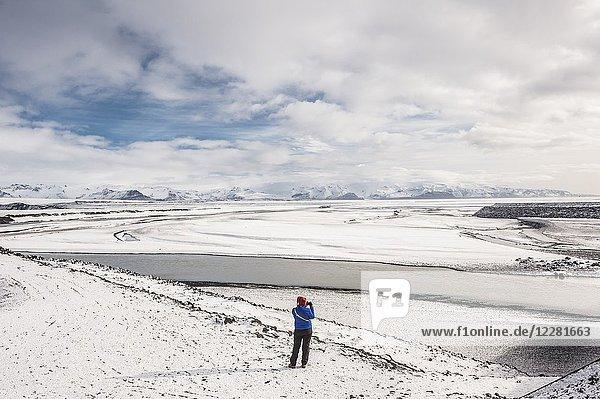 Young woman taking a picture in Gígjukvist glacier river and Skaftafellsfjöll mountains view in Skeidarársandur (region of Austurland  Iceland).