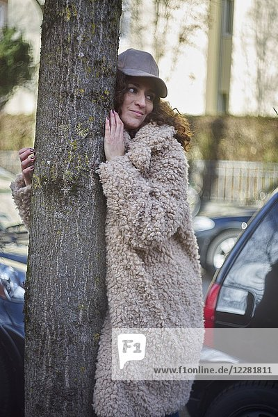 Multi-cultural woman embracing tree while standing in a city street full of cars. Wearing Coat and cap. Fashion blogger Aslihan Kiratli. Half German and half Turkish ethnicity. In Munich  Germany