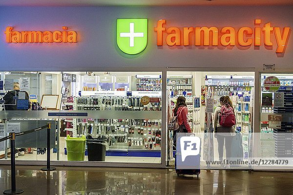 Argentina  Buenos Aires  Ministro Pistarini International Airport Ezeiza EZE  terminal concourse gate area  interior  shopping  concession  Farmacity  pharmacy  drug store  woman  rolling luggage  passenger  sign  entrance  Hispanic  Argentinean Argentinian Argentine South America American
