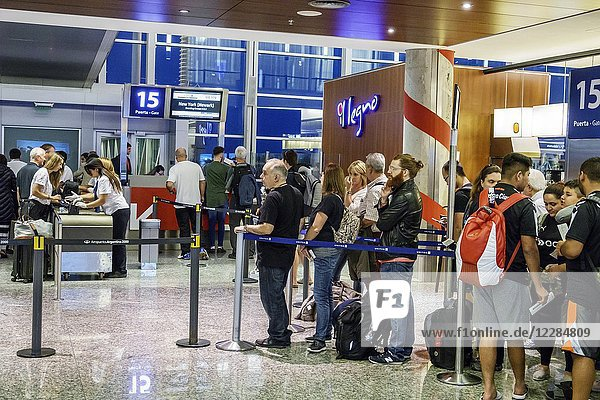 Argentina  Buenos Aires  Ministro Pistarini International Airport Ezeiza EZE  terminal concourse gate area  interior  security  boarding line  queue  passenger  man  woman  boy girl  teen  Hispanic  Argentinean Argentinian Argentine South America American