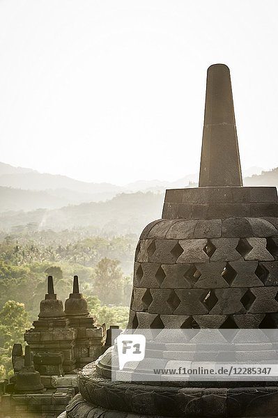 Unroofed pyramid of Borobudur Temple  crowned by bell-shaped stone domes (Magelang Regency  Central Java  Indonesia).