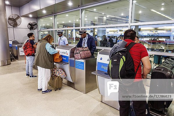 Florida  Miami  Miami International Airport MIA  terminal concourse gate area  American Airlines  sidewalk check-in  skycap  Black  man  woman  baggage check  luggage