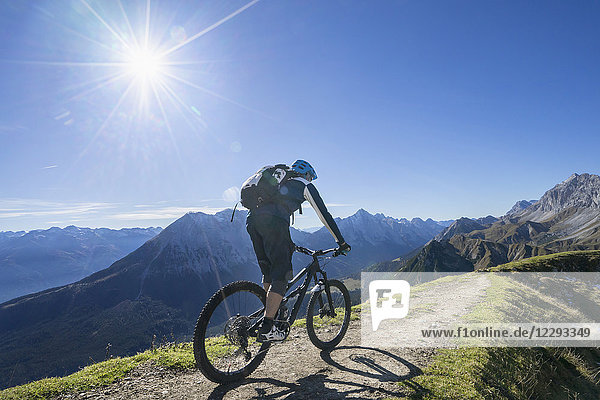 Mountain biker riding uphill in alpine landscape