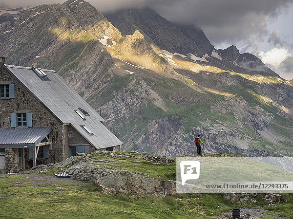 Woman hiking in the High Pyrenees standing on top of a little rock beside Refuge des Espuguettes  Gavarnie  France