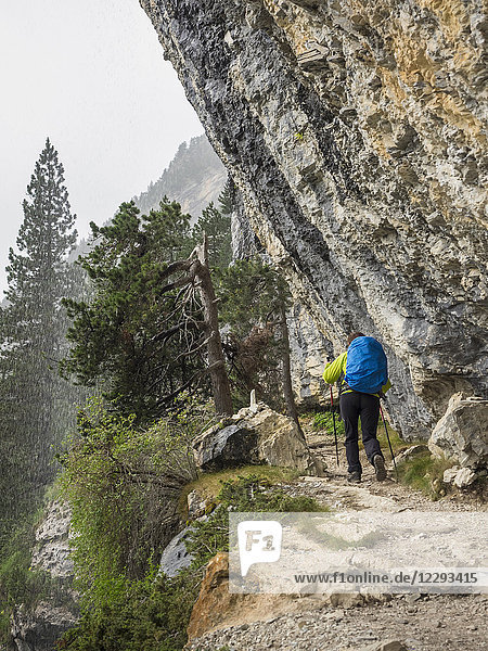 Woman hiking in the High Pyrenees on small path towards Refuge des Espuguettes  Gavarnie  France