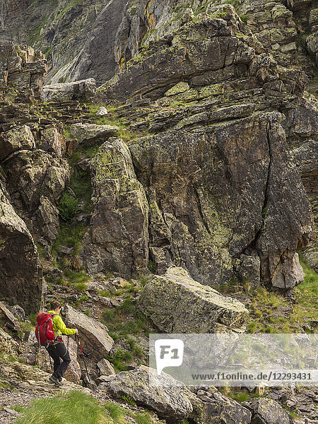 Woman hiking in the High Pyrenees descending from Hourquette d'Alans towards Cirque d'Estaube  Gavarnie  France