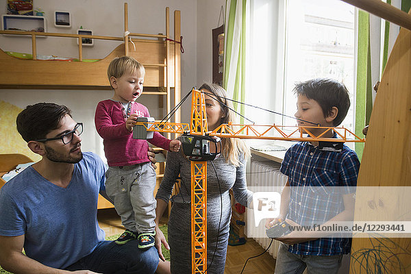 Two brothers and parents are playing with a toy crane  Munich  Germany