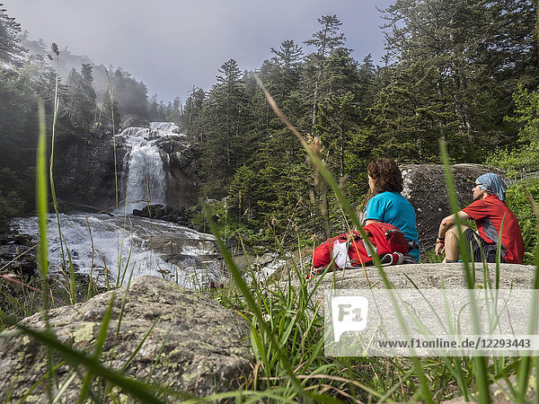 Hikers admiring scenic view of waterfall in Gave De Gaube river  France