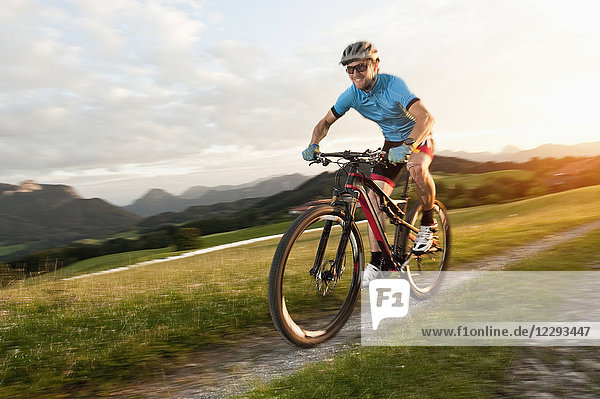 Mountainbiker rides at sunset in alps