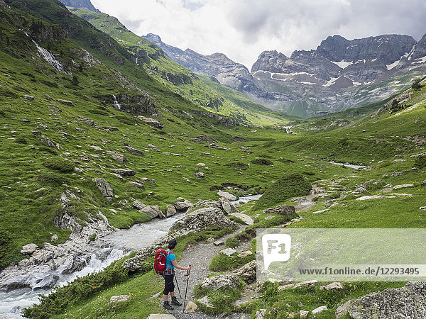 Woman hiking in the High Pyrenees with cirque d'Estaube in the background  Gavarnie  France