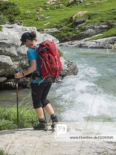 Woman hiking in the High Pyrenees walking on river shore of Gaube d'Estaube  France