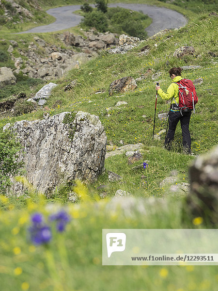 Woman hiking in the High Pyrenees on small path near Cirque de Troumouse  France