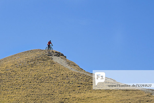 Mountain biker riding down hill in alpine landscape