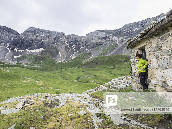 Woman hiker admiring scenic view of Cirque de Troumouse from mountain hut  France