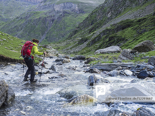 Woman hiking in the High Pyrenees near Cirque de Troumouse  crossing wild river  France