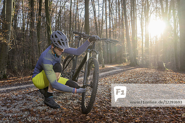 Mountain biker fixing front wheel of his bike on forest path