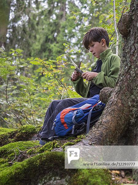 Girl carving a block of wood using knife in black forest  Feldberg  Baden-Württemberg  Germany