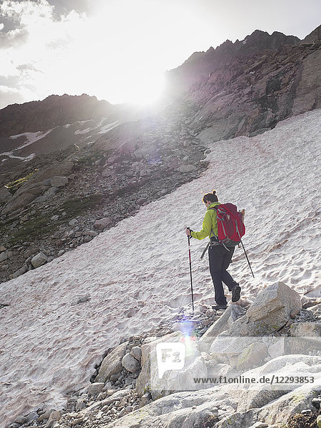Woman hiking in the High Pyrenees crossing snow field while ascending to mount Vignemale  Cauterets  France
