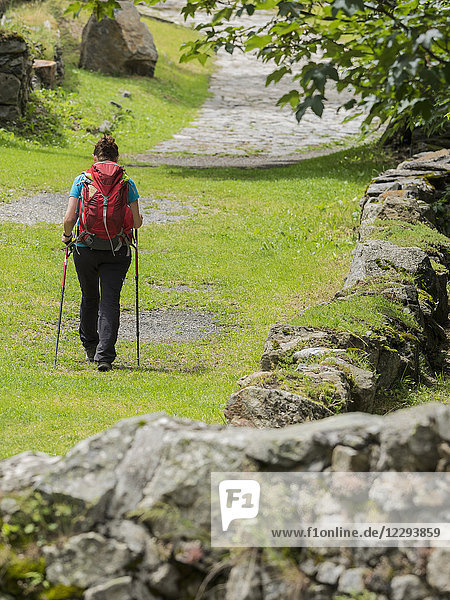 Woman hiking in the High Pyrenees on old road in village of Heas  France