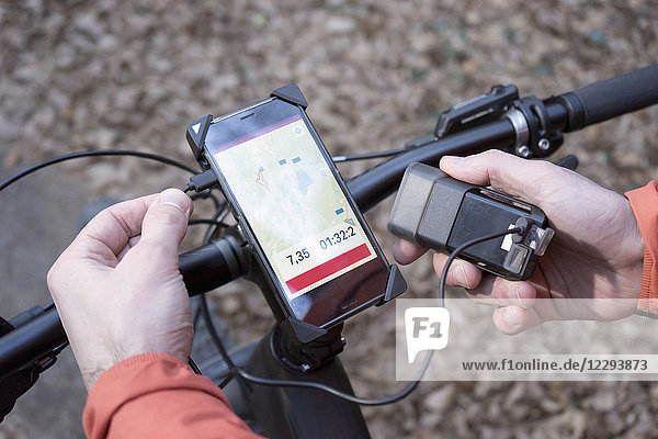 Mountain biker connecting GPS gear with external battery charger