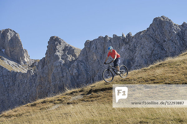 Mountain biker riding down hill in alpine landscape