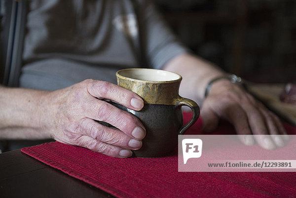 Hands of senior man holding pottery mug Hands of senior man holding pottery mug