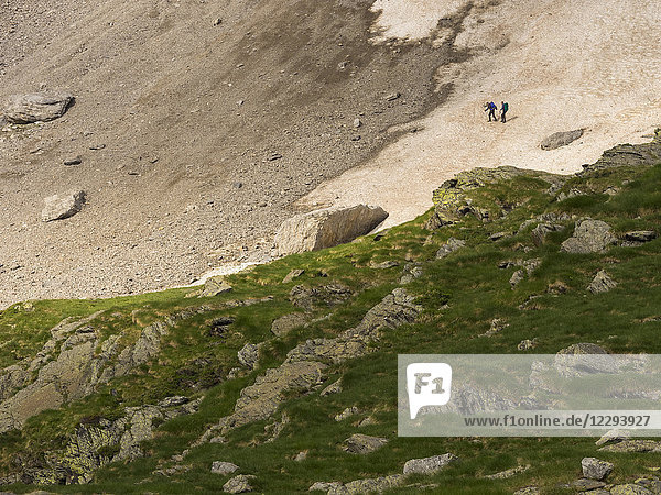 Two men hiking in the High Pyrenees crossing snow field near Hourquette d'Alans on their way to Cirque d'Estaube  Gavarnie  France