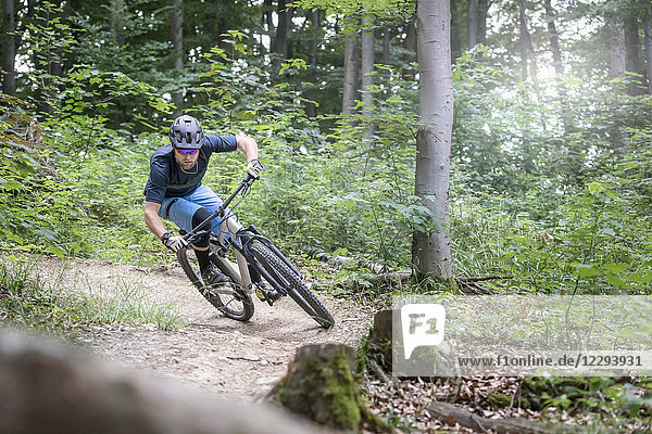 Mountain biker riding down hill on single track in forest
