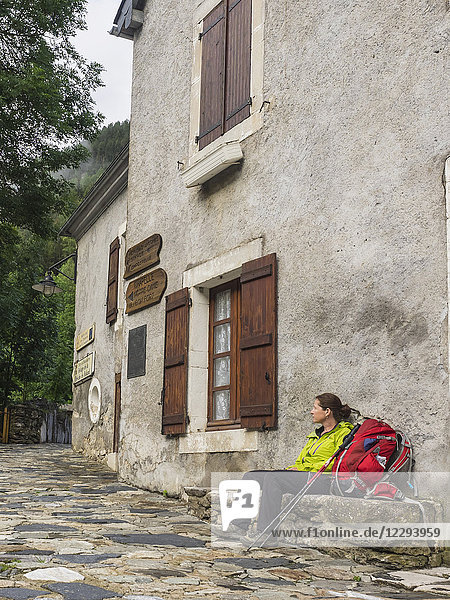 Woman hiker taking rest on a bank in front of an old building in the village of Gavarnie  France