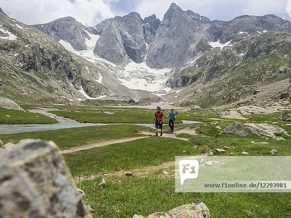 Man and woman hiking in the High Pyrenees in front of mount Vignemale  Cauterets  France
