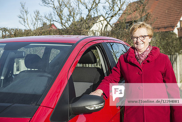 Portrait of old woman standing beside car