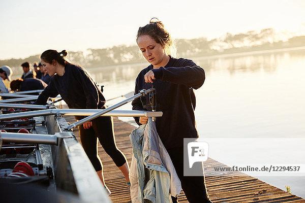 Rudererinnen bereiten den Schädel am sonnigen Ufer des Sees vor.