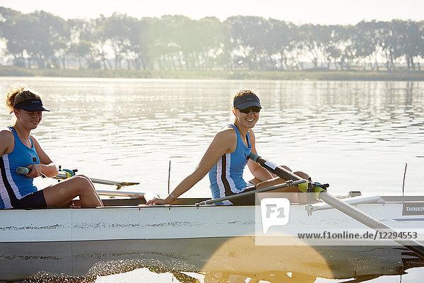 Portrait lächelnde Ruderin im Totenkopf am sonnigen See