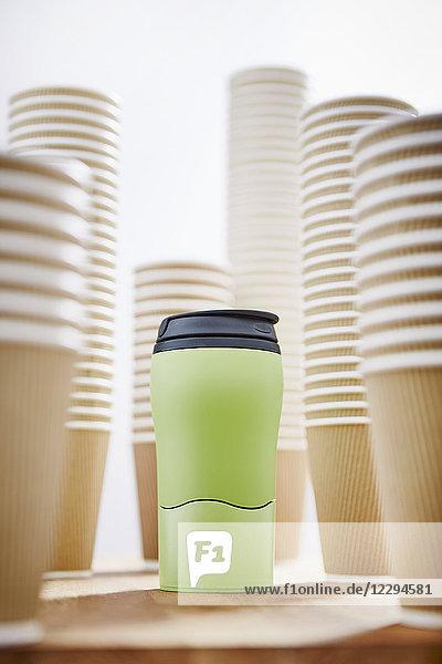 Grüner isolierter Getränkebehälter umgeben von Einweg-Kaffeetassen