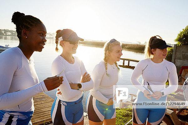 Weibliches Ruderteam am sonnigen Seeufer stehend