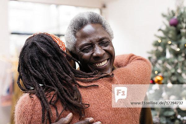 Glückliches älteres Paar  das sich in der Nähe des Weihnachtsbaums umarmt.
