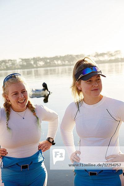 Rudererinnen mit Händen auf der Hüfte am sonnigen Seeufer