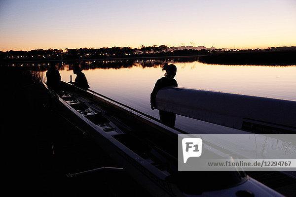 Weibliches Ruderteam mit Schädel am Sonnenaufgangssee