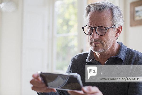 Focused mature man using smart phone