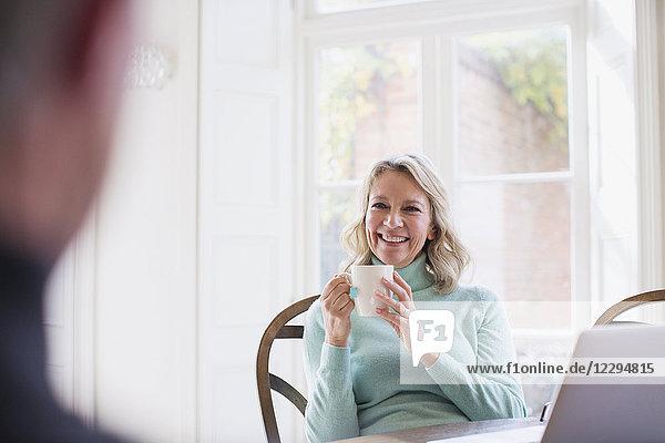 Smiling mature woman drinking tea  talking to man